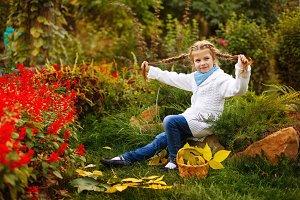 Girl plays fool in autumn park.