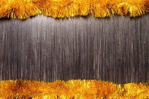 Gold tinsel on dark wood surface. Christmas decoration.