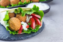 Chickpea falafel balls with vegetables and sauce, roll sandwich preparation, horizontal