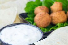 Chickpea falafel balls with vegetables and sauce, roll sandwich preparation