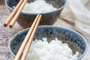 Cooked rice in ceramic bowl and chopsticks, vertical