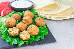 Chickpea falafel balls on slate board with vegetables and sauce, horizontal
