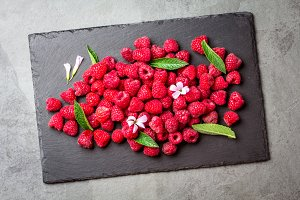 Berry raspberries with fresh mint leaves, edible flowers, black slate