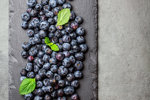 Berry blueberry with fresh mint leaves on black slate, top