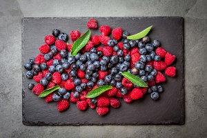 Berries raspberries and blueberries with fresh mint leaves, slate background