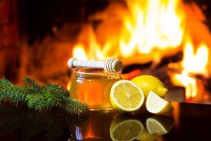 Jar of honey, lemon, fir branches, fireplace. Christmas composition