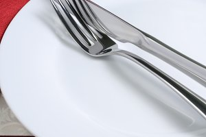 Knife and fork on a white plate