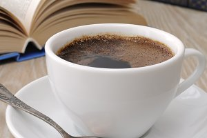 cup of coffee on a table among book