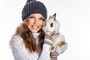Girl in knitted hat hold rabbit
