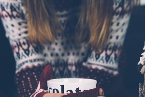 Young woman in sweater holding mug