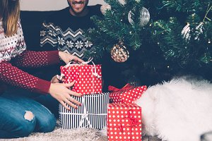 Young couple with stack of presents