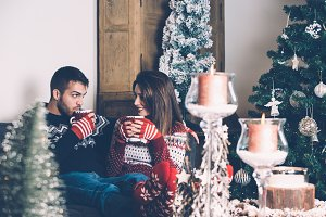 Couple sitting together with hot drinks