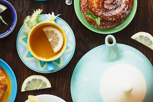 Cup with tea, teapot and baked goods