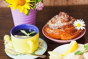 Cup with tea, ginger root and baked goods