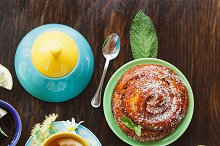 Tea set: Green tea with lemon and mint and baked goods with a crispy crust on the wooden background