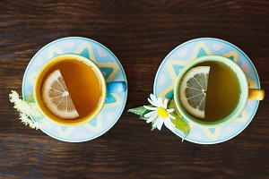 Two cups with tea on the wooden background