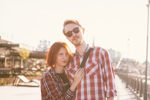 man and woman in the plaid shirt hugging on the background of the city