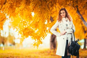 young girl in a light coat on the background of autumn park