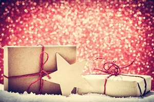 Retro rustic Christmas gifts, presents in snow on glitter background