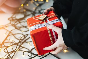 girl holding a Christmas gift in hand