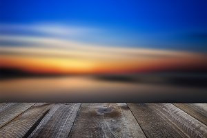 Wooden table and sunset over the sea