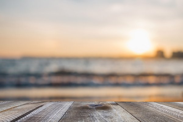 Wooden table and sunset over the se…