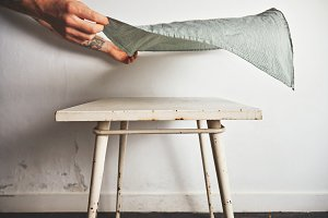 Putting tablecloth on old white table