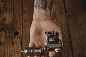 Close up of a man's hand with  tattoo gun