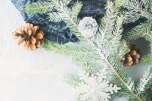 Winter background with fir tree branches and pine cones