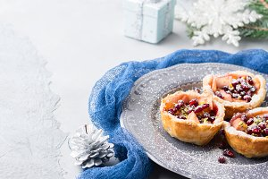 Christmas mini apple pies with pomegranate. Copy space