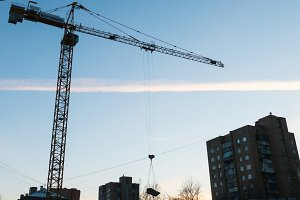 Construction crane with a load on the construction of a new home