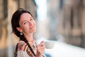 Portrait of beautiful girl with cup of coffee on the street. Caucasian tourist enjoy her european vacation in empty city