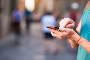 Closeup of male hands is holding cellphone outdoors on the street. Man using mobile smartphone.