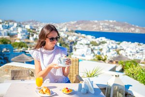 Beautiful elegant lady having breakfast at outdoor cafe with amazing view on Mykonos town. Woman snjoy her hot tea early in the morning