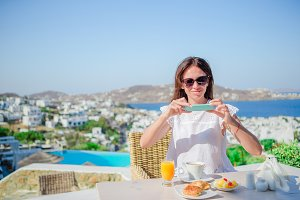 Woman taking photo of breakfast using her phone with amazing view of Mykonos. Girl taking pictures of food on luxury travel vacation for social media.
