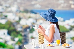 Beautiful elegant girl having breakfast at outdoor cafe with amazing view on Mykonos town. Woman drinking hot coffee on luxury hotel terrace with sea view at resort restaurant.