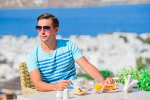 Young boy having breakfast at outdoor cafe with amazing view on Mykonos town. Man drinking hot coffee on luxury hotel terrace with sea view at resort restaurant.