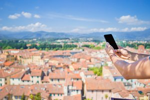 Closeup of male hands is holding cellphone background old italian town. Man using mobile smartphone.