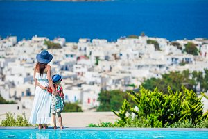 Adorable little girl and young mom on the edge of pool background greek town on Cyclades, Greece