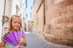 Adorable happy little girl taking selfie outdoors in european city. Portrait of caucasian kid enjoy summer vacation in old city