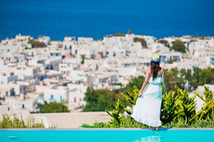 Beautiful young woman relaxing near pool with amazing view on Mykonos, Greece