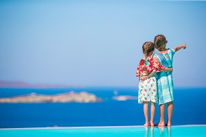 Adorable little girls on the edge of outdoor swimming pool with amazing view of old Mykonos town, Europe