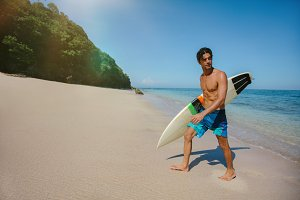 Male surfer holding surf board