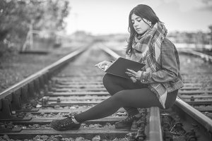 Young girl reading in railroad