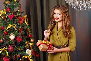 Girl unpacks gift. Christmas tree