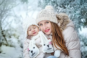 Mother holds daughter in winter