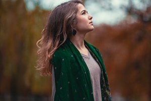 Portrait of a young girl with  green scarf on the background  autumn park.