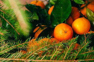 many fresh mandarins and branches of  Christmas tree on a wooden background