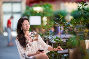 Portrait of beautiful woman sitting in outdoor cafe drinking coffee and using smartphone