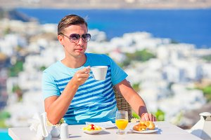 Young boy with hot coffeeat in outdoor cafe with amazing view on Mykonos town.